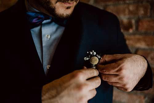 Bräutigam steckt sicheine Blume an