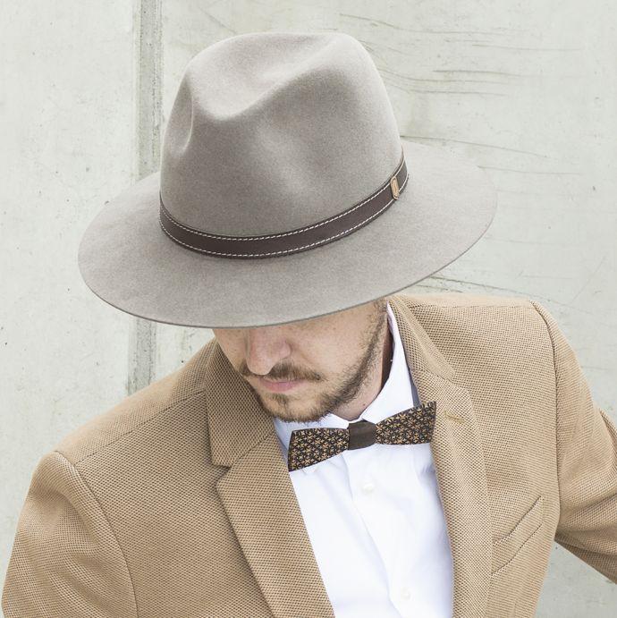 Ein Mann mit braunem Apis Hut mit brauner Jacke