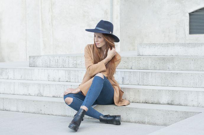 Eine Frau mit dunkelblauem Stellia Hut in Jeans und braunem Mantel