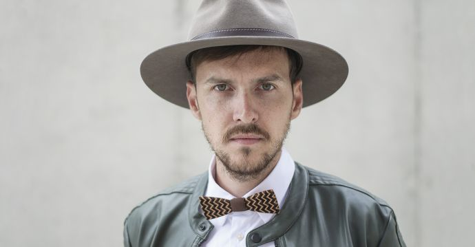 Ein Mann mit braunem Apis Hut in Lederjacke mit der Decorum Holzfliege