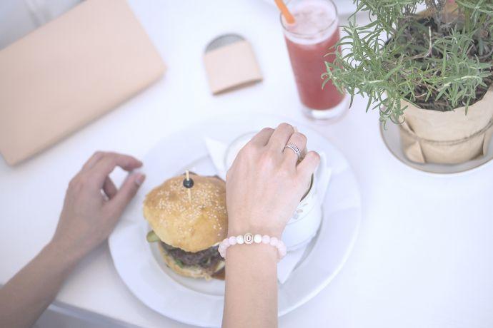 Mittagessen im Restaurant auf dem Tisch liegt die Leder Lady Lux Clutch Handtasche und ein Holzspiegel Liti