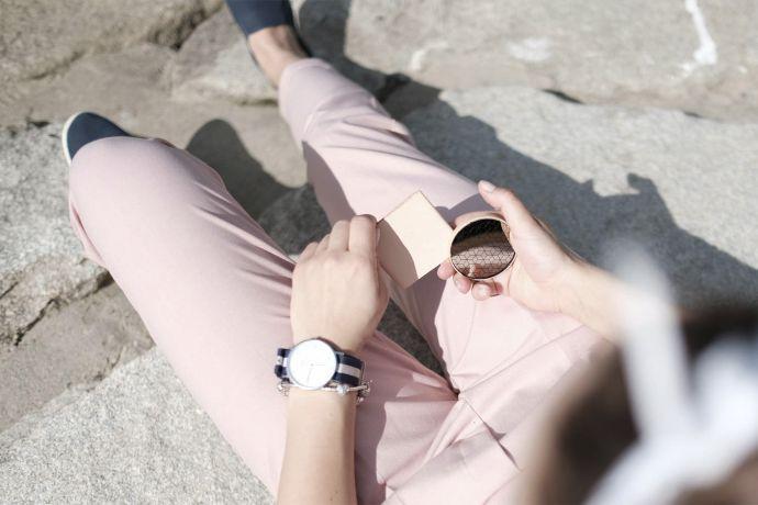 Model in rosa Hose mit Holzspiegel Liti in der Hand