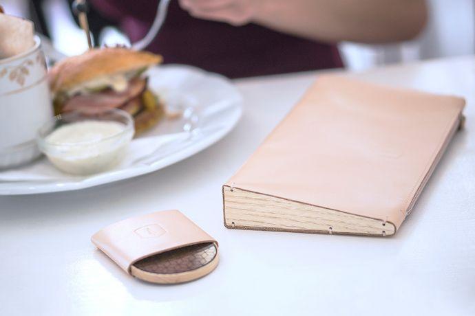 Die Lux Clutch Handtasche aus Leder mit Holzdetail und Holzspiegel Liti in einem Restaurant auf dem Tisch