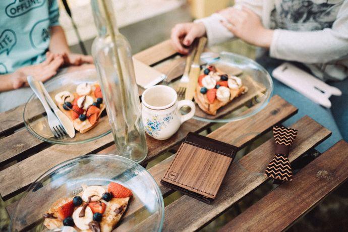 Das Nox Virilia Holzportemonnaie und die Trio Holzfliege auf dem Tisch im Restaurant