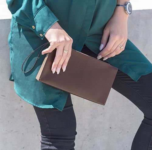 A brown-haired woman with an elegant leather clutch bag