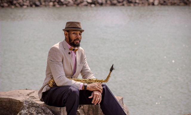 Der Musiker Saxappeal sitzt auf einem Stein mit einem Hut und der Bellis Fliege hält ein Saxophon in der Hand