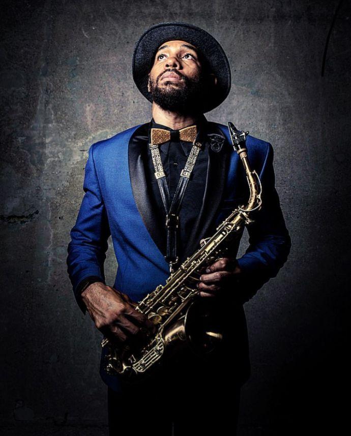Der Musiker Saxappeal in einer blauen Jacke mit einem Hut und der Bellis Holzfliege hält ein Saxophon in der Hand
