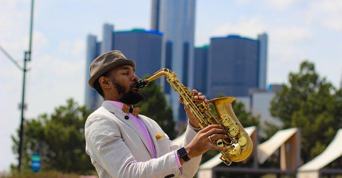 Der Musiker Saxappeal spielt Saxophon mit einem Hut und der Bellis Holzfliege