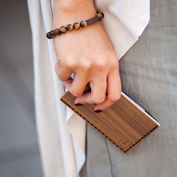 Eine Frau mit dem Kartenhalter aus Holz Nox Note in der Hand
