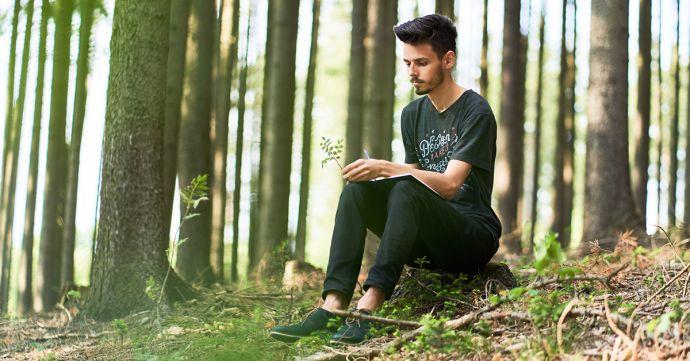 Ein Mann sitzt in einem Wald und schreibt in sein BeWooden Notizbuch