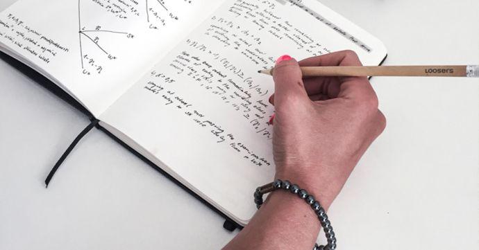 Frau mit dem Silver Hematit Armband schreibt in das Notizbuch