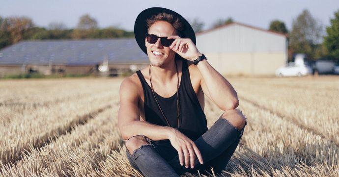 Ein Mann sitzt in einem Feld mit dem schwarzen Nox Hut
