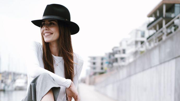 Eine Frau mit einem schwarzen Hut in der Stadt