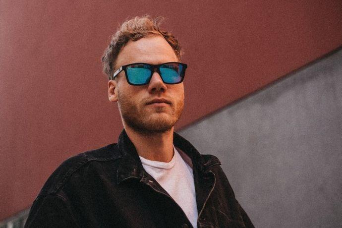 Junger Mann trägt eine Sonnenbrille mit blau getönten Gläsern
