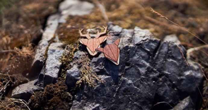 Zwei moderne Tierbroschen liegen auf einem vermoosten Stein
