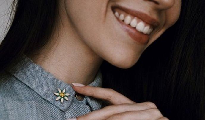 Lächelnde Frau trägt eine moderne Blumenbrosche am Kragen ihres Hemds