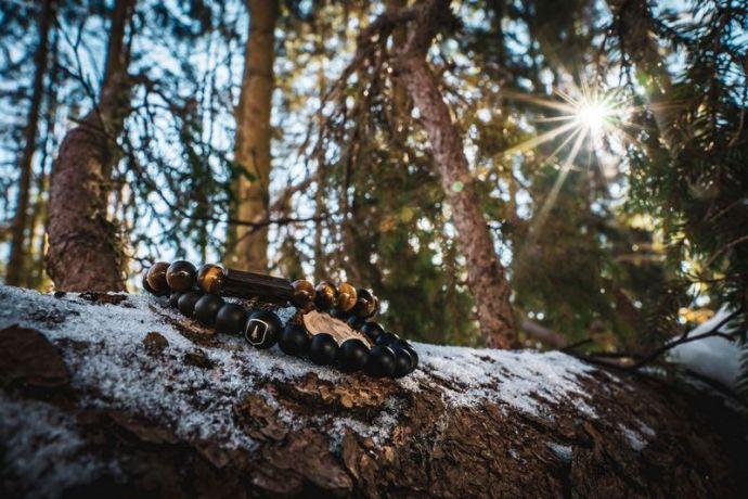 Zwei Armbänder liegen auf einem Ast im Wald