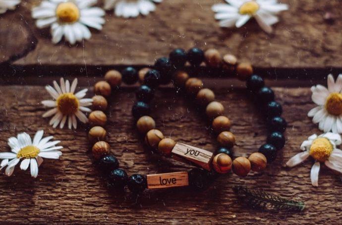 """Zwei Armbänder mit Gravur liegen auf einem Holzbrett. Auf dem einen ist """"love"""" eingraviert, und auf dem anderen ist """"you"""" eingraviert."""